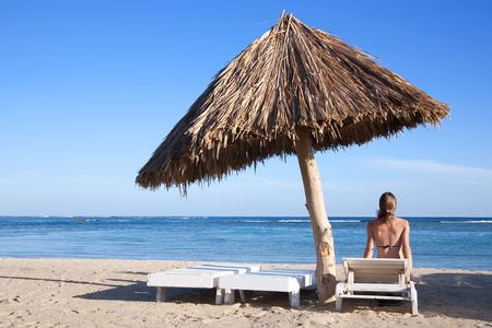 Woman sunbathing on deck chair at the resort beach photo