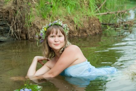 seamaid: Pretty girl  in flower chaplet at river Stock Photo