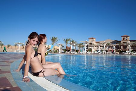 Two young girls in  swimming pool at resort hotel