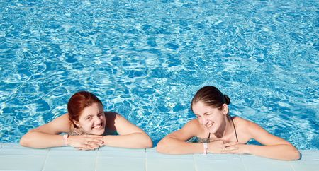 Two happy girls in  swimming pool at resort hotel photo