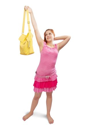 Happy girl in pink dress with yellow handbag over white photo