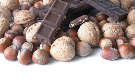 nit: brown nuts and stick of chocolate over white Stock Photo