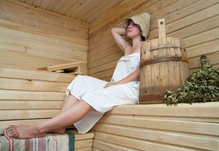 Young woman is taking a steam-bath  at sauna   photo