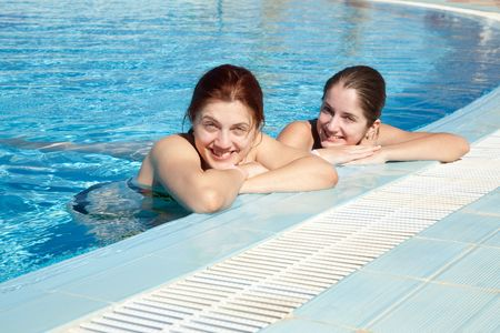 Two young girls in  swimming pool at resort hotel photo