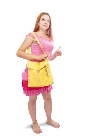 girl in pink dress with yellow handbag pointing away photo