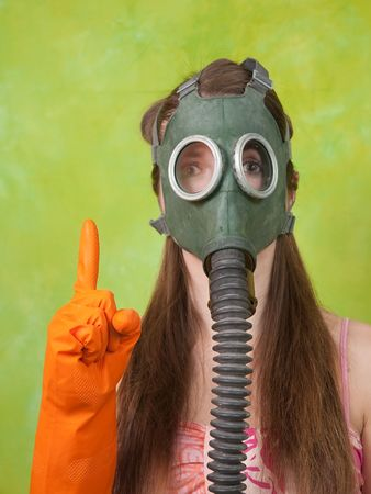 gas mask: girl in gas mask pointing ATTENTION over green background