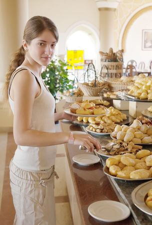 girl chooses sweet meal in buffet at hotel photo
