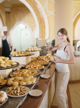 breakfast hotel: girl chooses sweet pastry  in buffet at hotel