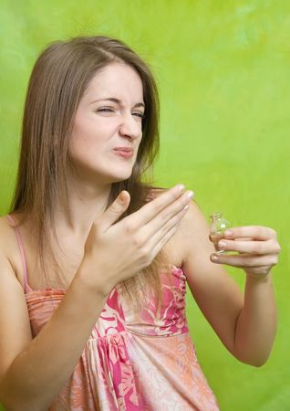 Beautiful young woman smelling bad perfume  photo