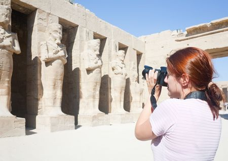 Girl is photographing an ancient statues in Karnak temple, Luxor, Egypt photo