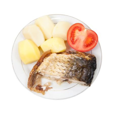Grilled carp fish with potatoes and tomato on the white plate over white photo
