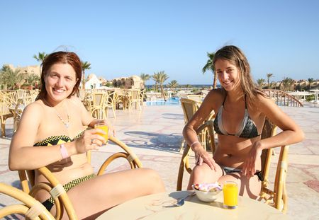 Girls relaxing with orange juice  at resort hotel photo