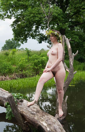 Nude girl  in  flowers wreath  on sheared tree Stock Photo - 6289315