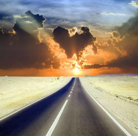 Road door woestijn landschap onder bewolkte hemel  Stockfoto
