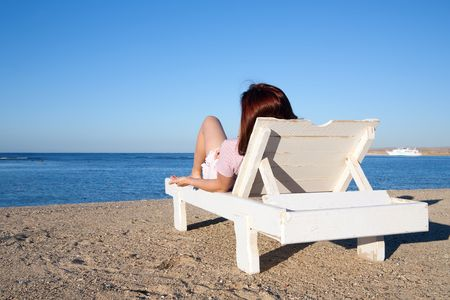 beauty woman  relaxing in deck chair at resort beach photo