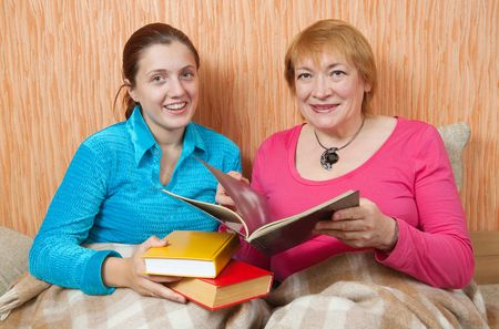 woman and her adult daughter sitting in the sofa and reading a book together  photo