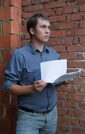 tasker:  businessman with a documents against  the brick wall