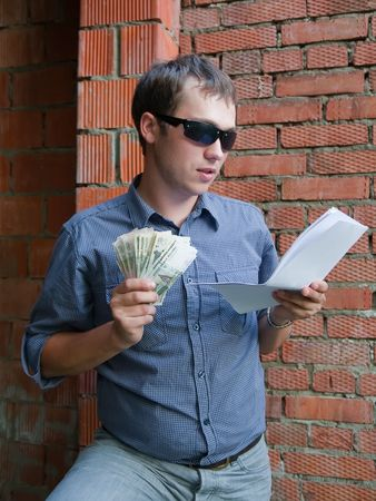 tasker: Happy worker with documents and money  against  the brick wall