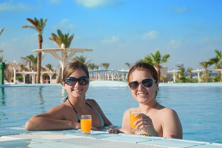 Girls relaxing in tropical pool with orange juice  at resort hotel photo