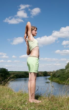 Beautiful young girl practicing yoga  against blue sky Stock Photo - 6346255