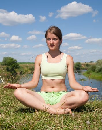 Beautiful young girl practicing yoga against river Stock Photo - 6346505