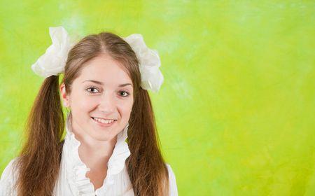Portret van lange-haired school meisje op groene achtergrond
