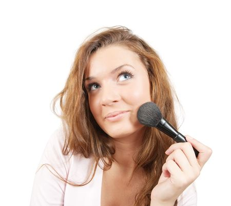 Girl putting facial powder on her face with a brush, white background. photo