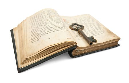 guide book: key placed on an 18st century vintage book, isolated on white