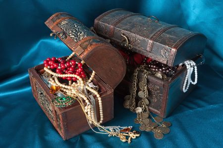 earing: Two wooden treasure chests with valuables on blue textile Stock Photo