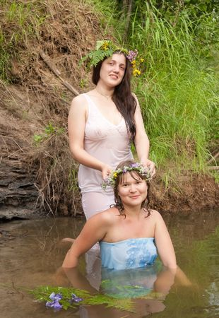 woman's clothing: Two girls in  flower wreath  at river Stock Photo