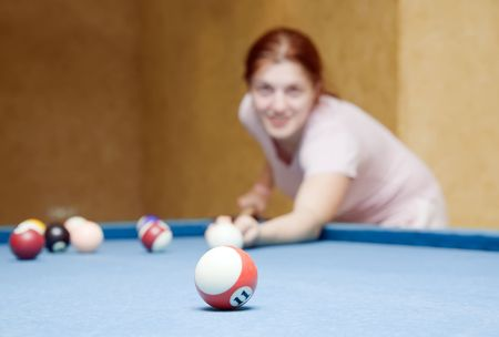 young woman playing billiards looking at camera. Focus on ball photo