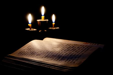 old Psalter and candles in candelabrum against black photo