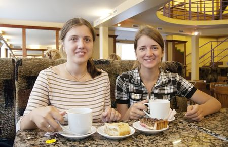 Beautiful girls relaxing at coffee-room with a cup of tea  photo