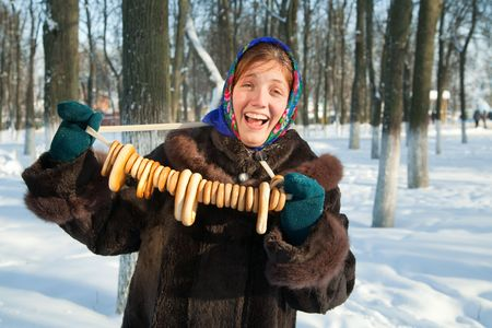 Happy girl in  fur coat with round cracknel against  winter rural landscape Stock Photo - 6429091
