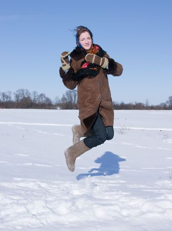 girl in russian traditional clothes jumping against  winter landscape