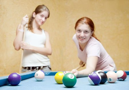 focal point:  women playing billiards. Focal point on ball Stock Photo