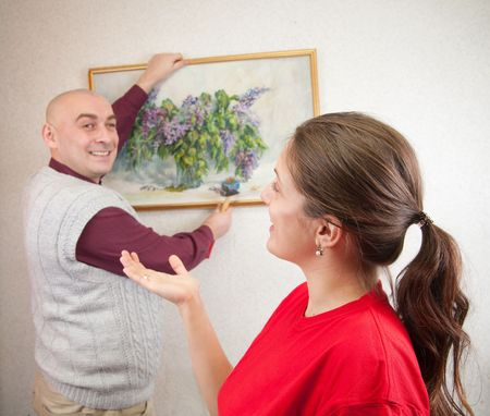 attempting: An attractive young man and her wife attempting to hang an art picture. Focus on girl   Stock Photo