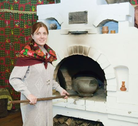 Woman puts a pot into russian stove. Interior of russian house with oven  photo