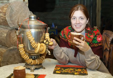 Woman near  traditional russian samovar in russian traditional interior photo