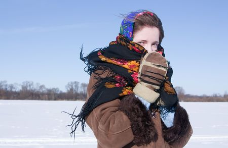 kisser: Smiling girl in russian traditional kerchief  against  winter landscape