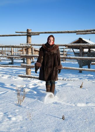 girl in russian traditional clothes against  winter village landscape photo