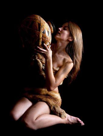 primitivism: Female cave-dweller in foxcase with jug at dark