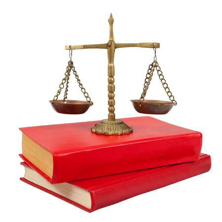 Scales of justice atop legal books over white