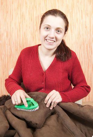 sheepskin: Mujer joven limpieza un sheepskin con batidor de escoba en el hogar Foto de archivo