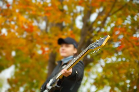 girl with electric bass guitar against autumn nature, Focus on guitar only photo