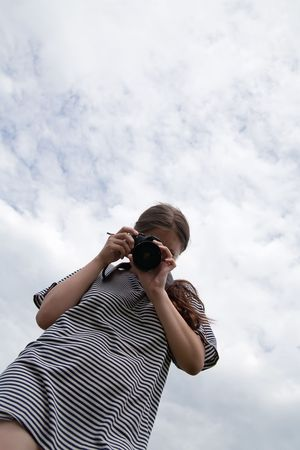 Young female photographer  against cloudy sky Stock Photo - 6498524