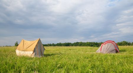 Two tourist tents on medow against nature photo