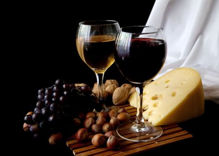 Grapes and cheese with glass of red wine on a black background photo