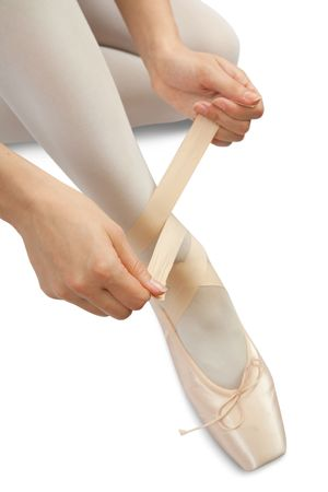pointe shoes: Closeup of  Ballerina putting on pointes over white  Stock Photo