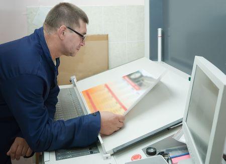 Printer checking a print run at table Stock Photo - 6498897